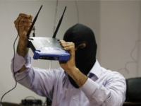 A masked Lebanese secret service officer shows to the media at the Lebanese security services headquarters in Beirut on May 11, 2009 a wireless internet router found with arrested Lebanese nationals accused of spying for Israel.