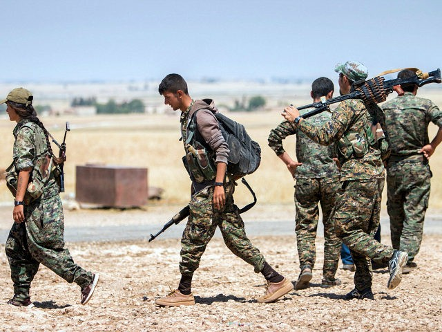 Kurdish People's Protection Units (YPG) fighters walk with their weapons at the eastern entrances to the town of Tal Abyad in the northern Raqqa countryside, Syria, June 14, 2015, after taking control of nearby Suluk town from Islamic State fighters. REUTERS/RODI SAID