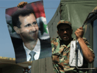A Syrian soldier waves a picture of the Syrian president, Bashar Assad, as he crosses the Lebanese-Syrian border April 26, 2005 in Jdaidet Yabous, Syria.