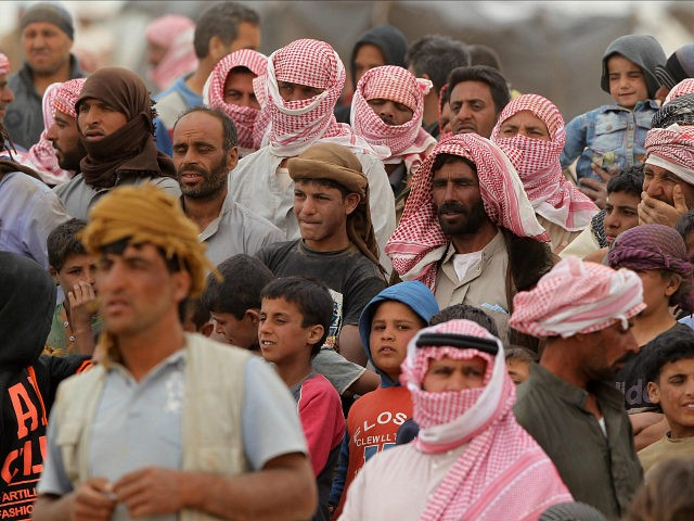 JORDAN, Royashed Town : Syrian refugees wait to cross to a camp at the Jordanian side of the Jordan-Syria border near Royashed Town in Jordan on May 4, 2016.