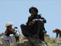 In this Friday, May 27, 2016 photo, Taliban fighters guard as senior leader of a breakaway faction of the Taliban Mullah Abdul Manan Niazi, not pictured, delivers a speech to his fighters, in Shindand district of Herat province, Afghanistan. In the rugged terrain of the Taliban heartland in southern Afghanistan, the fight against Kabul has become a war for control of key stretches of main roads and highways as the insurgents use a new tactic to gain ground. (AP Photos/Allauddin Khan)