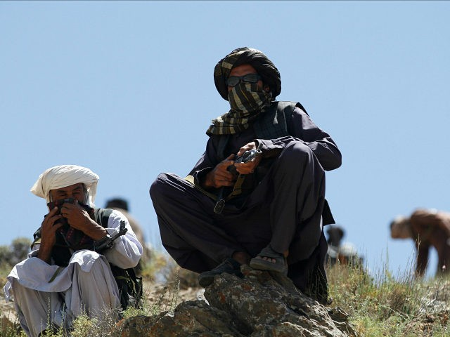 In this Friday, May 27, 2016 photo, Taliban fighters guard as senior leader of a breakaway faction of the Taliban Mullah Abdul Manan Niazi, not pictured, delivers a speech to his fighters, in Shindand district of Herat province, Afghanistan. In the rugged terrain of the Taliban heartland in southern Afghanistan, …