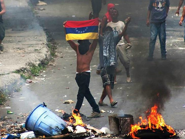 'La Vega' low income neighborhood residents clash with riot police during a demonstration in Caracas on June 10, 2016. Facing mounting pressure from food shortages, looting and increasingly violent protests, Venezuelan authorities on Friday announced the next stage for a recall referendum against embattled President Nicolas Maduro. / AFP / …