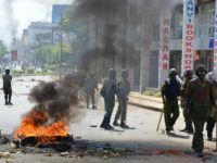Police officers walk past burning tyres in Kisumu, Kenya, on June 6, 2016