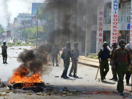 Police officers walk past burning tyres in Kisumu, Kenya, on June 6, 2016