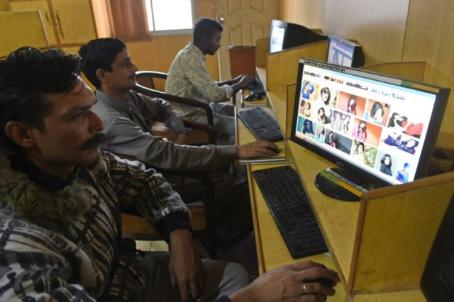 People in Pakistani look at internet images of Qandeel Baloch, who uploaded pictures of herself with Mufti Abdul Qavi