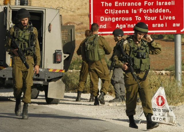 Israeli soldiers are seen at one of the entrances of the Palestinian village of Yatta in the occupied West Bank on June 9, 2016