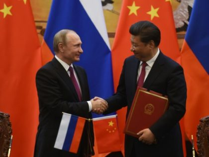 Russian President Vladimir Putin (L) shakes hands with Chinese President Xi Jinping during a signing ceremony in Beijing's Great Hall of the People on June 25, 2016