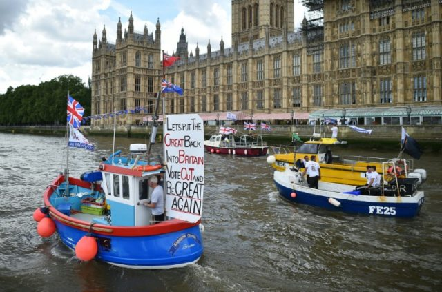 A Brexit flotilla of fishing boats passes the Houses of Parliament as it sails up the river Thames in London on June 15, 2016