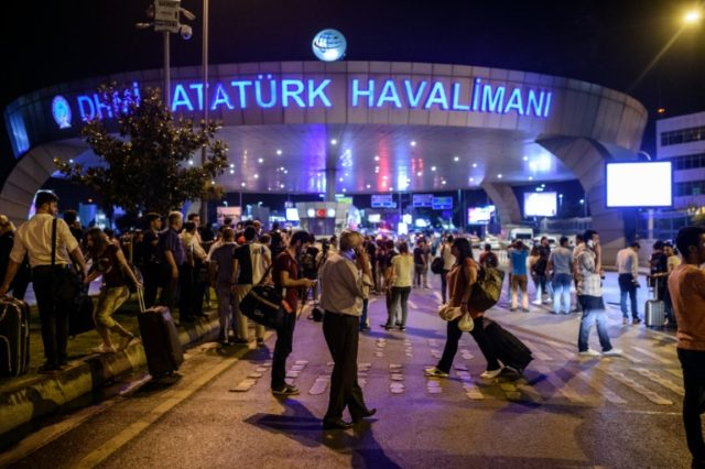 People stand outside the entrance as they leave the airport after two explosions followed by gunfire hit the Turkey's biggest airport of Ataturk in Istanbul, on June 28, 2016