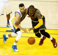 Golden State Warriors guard Stephen Curry (left) and Cleveland Cavaliers forward LeBron James scramble for a loose ball during game 1 of the NBA Finals on June 2, 2016 in Oakland, California