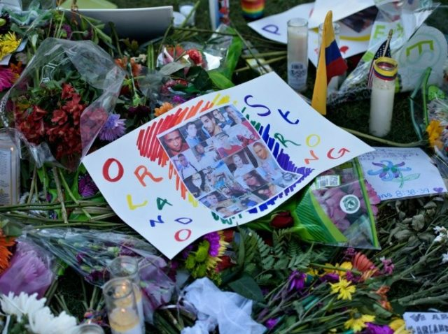 Photos and flowers are seen at a memorial to honor the Pulse nightclub mass shooting victims on June 14, 2016 in Orlando, Florida