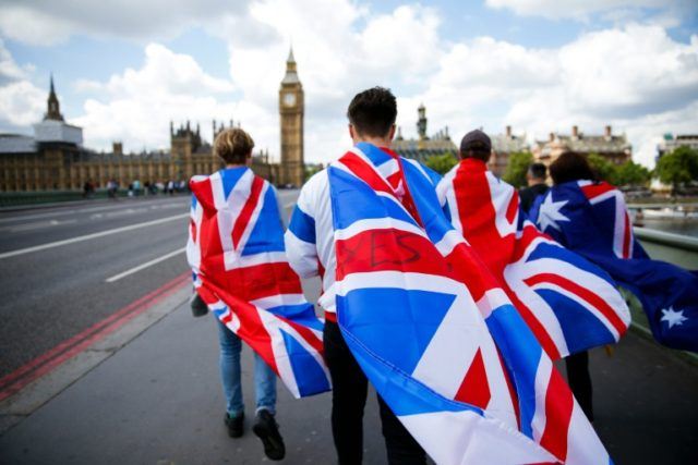 People walk over Westminster Bridge wrapped in Union flags, towards the Queen Elizabeth Tower (Big Ben) and The Houses of Parliament in London on June 26, 2016
