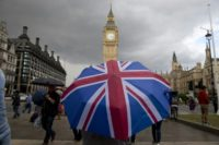 A pedestrian shelters from the rain beneath a Union Jack-themed umbrella near the Houses of Parliament in central London