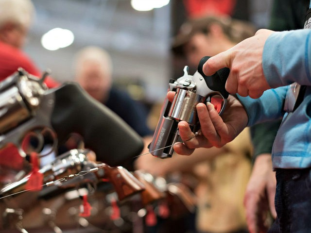An attendee handles a revolver in the Sturm, Ruger & Co., Inc. booth on the exhibition floor of the 144th National Rifle Association (NRA) Annual Meetings and Exhibits at the Music City Center in Nashville, Tennessee, U.S., on Saturday, April 11, 2015. Top Republican contenders for their party's 2016 presidential …