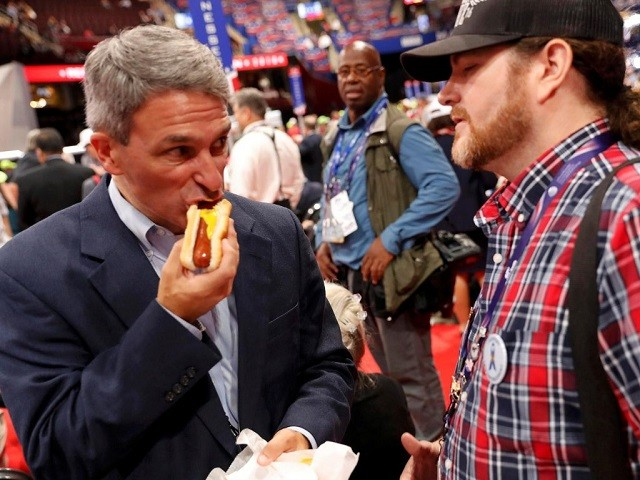 Former Virginia Attorney General Ken Cuccinelli sneaks in a quick hot dog on the floor of the Republican National Convention as he discusses a controversial fight over the RNC rules with a delegate (R) at the Republican National Convention in Cleveland, Ohio, U.S., July 18, 2016. REUTERS/Jonathan Ernst