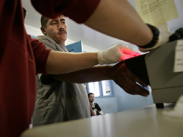 Allen J. Schaben –– – A Border Patrol agent scans an Illegal alien's fingerprint in the new Integrated Automated Fingerprint Identification System (IAFIS) as another waits in the processing room to be fingerprinted after being caught with a group of seven illegal aliens two miles east of the Otay Mesa …