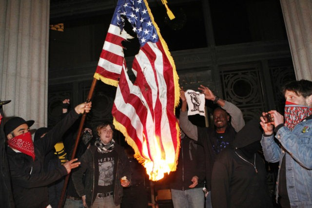 "In this Saturday, Jan. 28, 2012 file photo, Occupy Oakland protesters burn a U.S. flag found inside City Hall in Oakland, Calif. during a protest on its steps. ""Flags are, by their nature, emotion-charged emblems, and that's especially the case in the U.S.,"" says John Hartvigsen, president of the North …"