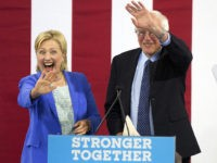 Democratic presidential candidate Hillary Clinton waves with her Democratic rival Sen. Bernie Sanders, I-Vt. during a rally Tuesday, July 12, 2016, in Portsmouth, N.H. (AP Photo/Jim Cole)
