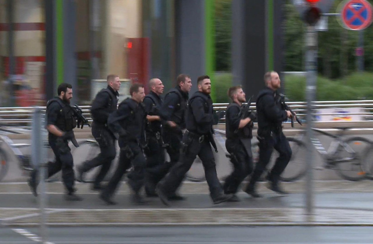 In this grab taken from video, police run in the area of the Olympia Einkaufszentrum mall, after a shooting, in Munich, Germany, Friday, July 22, 2016. A manhunt was underway Friday for a shooter or shooters who opened fire at a shopping mall in Munich, killing and wounding several people, a Munich police spokeswoman said. The city transit system shut down and police asked people to avoid public places. (AP)