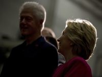 Former President Bill Clinton, left, and Democratic presidential candidate Hillary Clinton, right, are silhouetted by a light as they attend a factory tour of K'NEX, a toy company, in Hatfield, Pa., Friday, July 29, 2016. Clinton and Kaine begin a three day bus tour through the rust belt. (AP Photo/Andrew …