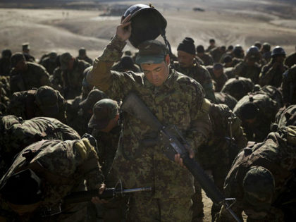 An Afghan Army soldier adjusts his helmet during an exercise at a training facility in the outskirts of Kabul, Afghanistan, Tuesday, Nov. 26, 2013. The Afghan National Security Forces depend exclusively on billions of dollars in funding from the United States and its allies, money that is now at risk …