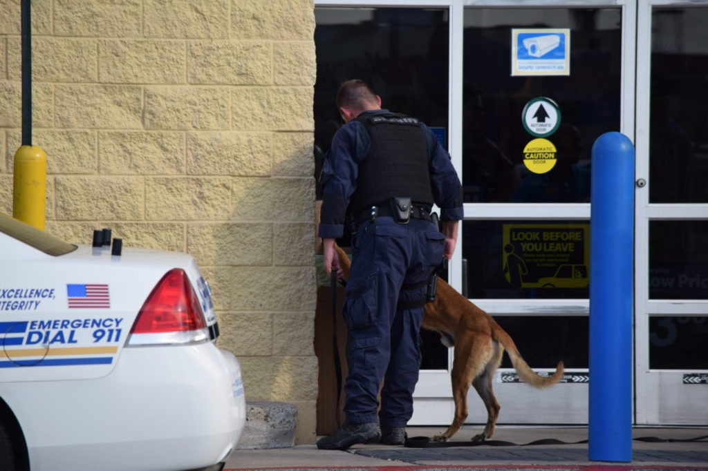 K-9 team searching the exterior of the Walmart store after a bomb threat. (Photo: Bob Price/Breitbart Texas)