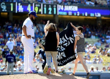 LOS ANGELES, CA - JULY 03: Protestors interupt the game as Kenley Jansen #74 of the Los Angeles Dodgers waits on the mound during the ninth inning against the Colorado Rockies at Dodger Stadium on July 3, 2016 in Los Angeles, California. (Photo by Harry How/Getty Images)