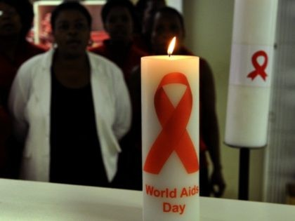 November 28, 2013 shows staff members of the Themba Lethu Clinic in Johannesburg, the largest antiretroviral treatment site in the country, posing behind candles commemorating World Aids Day (December 1). South Africa has been hailed as a model for HIV treatment, but some now fear its very success may be …
