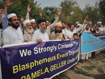 Pakistani residents shout slogans as they march behind a banner during a protest in Peshawar on May 5, 2015, against the anti-Muslim cartoon exhibition in Garland, Texas. The two gunmen shot dead when they attempted to storm an anti-Muslim cartoon exhibition have been identified as roommates from Arizona, one of …