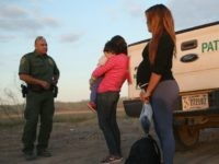 An immigrant from El Salvador, seven months pregnant, she said, stands next to a U.S. Border Patrol truck after she and others turned themselves in to border agents on December 7, 2015 near Rio Grande City, Texas. Many pregnant women, according to Border Patrol agents, cross illegally into the U.S. late into their terms with the intention of birthing their babies in the United States. All people born in the U.S. are American Citizens, according to the U.S. constitution. Border Patrol agents continue to detain hundreds of thousands of undocumented immigrants trying to avoid capture after crossing into the United States, even as migrant families and unaccompanied minors from Central America cross and turn themselves in to the Border Patrol to seek assylum. (Photo by