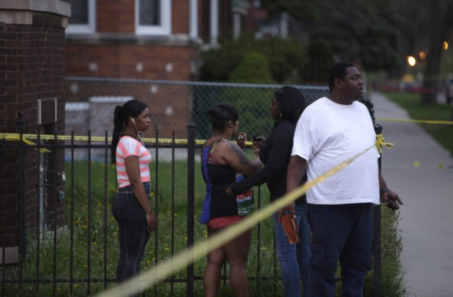 CHICAGO, IL - APRIL 25: People watch as Chicago Police officers and evidence technicians investigate the scene where a 16-year-old boy was shot in the head and killed and another 18-year-old man was shot and wounded on the 7300 block of South Sangamon Street on April 25, 2016 in Chicago, …
