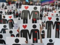 People hold placards depicting hearts and couples, during a flash mob for the annual Lesbian, Gay, Bisexual and Transgender (LGBT) Pride Parade in Milan, on June 25, 2016. / AFP / GIUSEPPE CACACE (Photo credit should read
