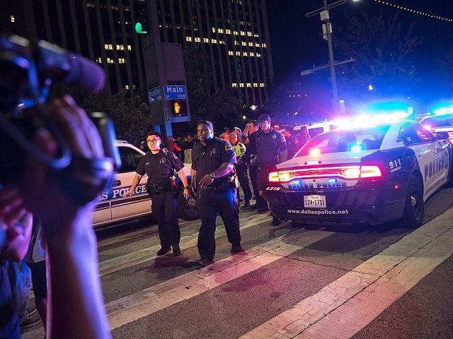 TOPSHOT - Bystanders stand near pollice baracades following the sniper shooting in Dallas on July 7, 2016. A fourth police officer was killed and two suspected snipers were in custody after a protest late Thursday against police brutality in Dallas, authorities said. One suspect had turned himself in and another …