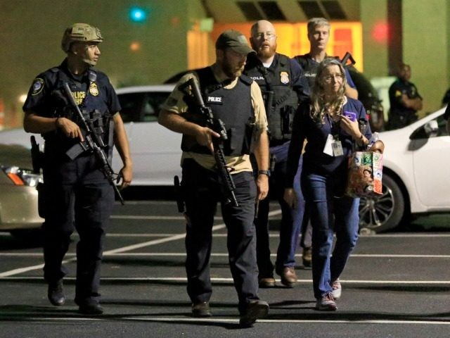 Dallas police officers escort a woman near the scene where eleven Dallas police officers were shot and five have now died on July 8, 2016 in Dallas, Texas)