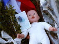 NICE, FRANCE - JULY 15: A childs doll sits next to a French flag and tributes to the victims of a terror attack on the Promenade des Anglais on July 15, 2016 in Nice, France. A French-Tunisian attacker killed 84 people as he drove a lorry through crowds, gathered to …