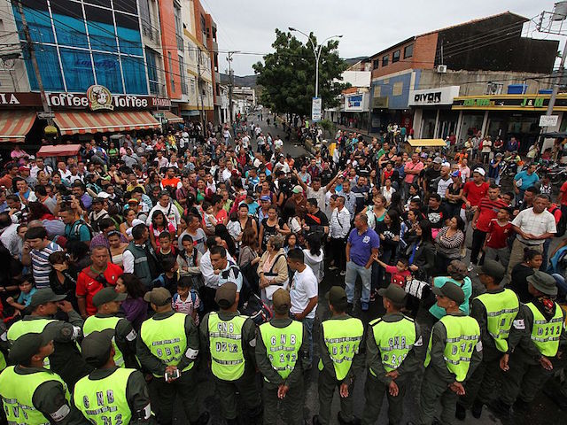 Venezuelans wait for their turn in San Antonio del Tachira, Venezuela, to cross to Cucuta, Colombia, through the Simon Bolivar bridge, to buy supplies on July 16, 2016. Thousands of Venezuelans crossed into the Colombian city of Cucuta to buy food and medicine, taking advantage of another brief opening in the border that's been closed nearly a year. Caracas authorized the temporary opening a week after some 35,000 Venezuelans poured across the border during a 12-hour opening of the pedestrian bridge. / AFP / GEORGE CASTELLANOS (Photo credit should read GEORGE CASTELLANOS/AFP/Getty Images)