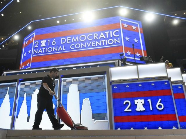 A worker vacuums the stage prior to the start of Day 1 of the Democratic National Convention at the Wells Fargo Center in Philadelphia, Pennsylvania, July 25, 2016. / AFP / SAUL LOEB (Photo credit should read