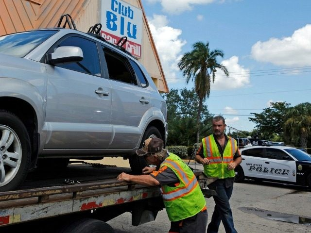 FORT MYERS, FL - JULY 25: Police remove a car hit by gunfire outside of Club Blu where two people were killed and at least 15 wounded on July 25, 2016 in Fort Myers, Florida. (Photo by