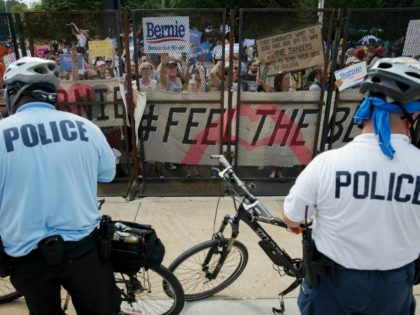 People protest through a security fence outside of the Wells Fargo Center, venue of the 2016 Democratic National Convention, during march holding signs in support of former Democratic presidential candidate Bernie Sanders during a protest outside the DNC, July 25, 2016 in Philadelphia, Pennsylvania. / AFP / Patrick T. Fallon (Photo credit should read