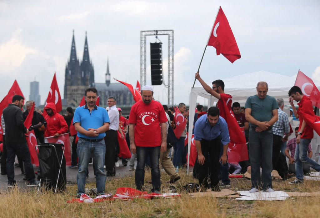 Supporters of Turkish President Recep Tayyip Erdogan pray ahead of a rally on July 31, 2016 in Cologne, as tensions over Turkey's failed coup put authorities on edge. Police said some 20,000 people had joined in the demonstration staged by groups including the pro-Erdogan Union of European-Turkish Democrats (UETD). / AFP / DPA / Oliver Berg / Germany OUT (Photo credit should read OLIVER BERG/AFP/Getty Images)