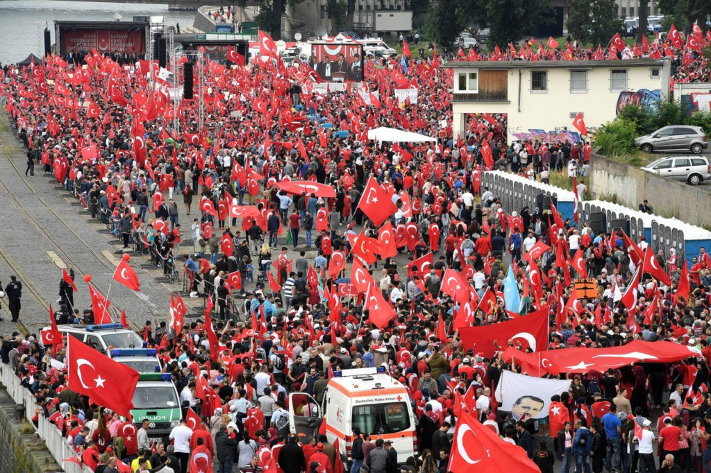 COLOGNE, GERMANY - JULY 31: Supporters of Turkish President Recep Tayyip Erdogan rally at a gathering on July 31, 2016 in Cologne, Germany. Cologne and surrounding cities are home to tens of thousands of people of Turkish descent. Erdogan has pursued strong-handed measures following the recent coup attempt by elements of the Turkish armed forces that include the shuttering of media outlets and the arrest of journalists as well as suspensions of ten of thousands of university professors, public servants and police members. (Photo by Sascha Steinbach/Getty Images)