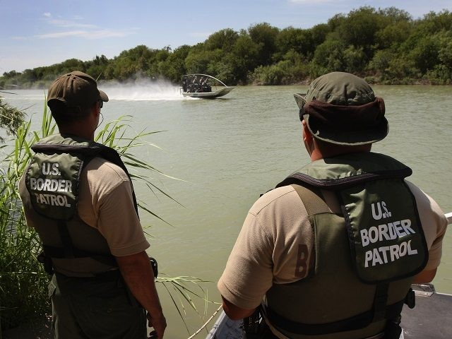 "LAREDO, TX - AUGUST 07: U.S. Border Patrol agents watch colleagues motor past while patrolling for illegal immigrants in the Rio Grande River crossing into the United States August 7, 2008 near Laredo, Texas. Agents in the Laredo sector of the border travel the Rio Grande River in six 18"" …"