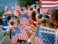 People wave flags as the Independence Day parade rolls down Main Street, Friday, July 4, 2014, in Eagar, Ariz. The Northern Arizona town celebrates the Fourth of July annually with a parade and fireworks.