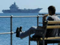 A man enjoy the sea and the sun as in the background the Russian aircraft carrier Admiral Kuznetsov lies at anchor off Cyprus' largest port of Limassol on Thursday, Feb. 27, 2014. The aircraft carrier arrived in Cyprus for a three-day rest and resupply stay. (AP Photo/Pavlos Vrionides)