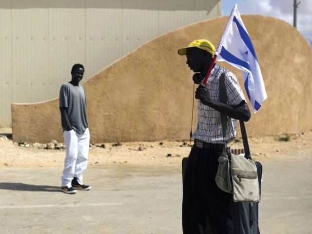 An African migrant holds an Israeli flag after being released from the Holot detention center in the Negev. (photo credit:REUTERS)