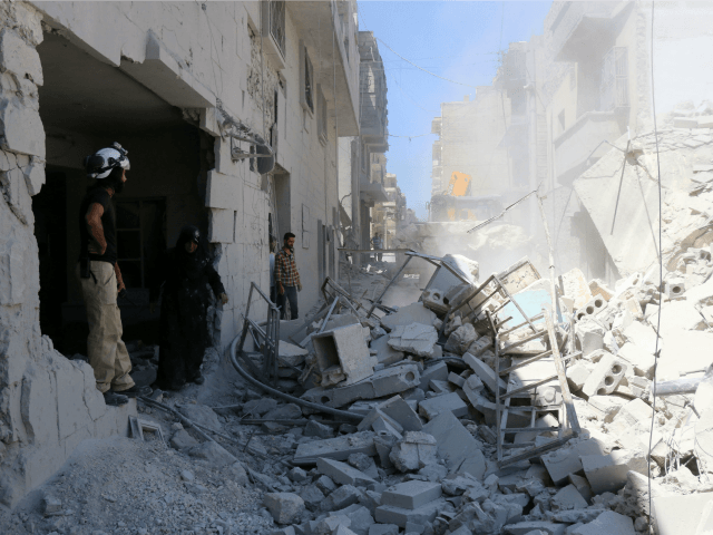 Syrians look at civil defence workers using a digger to look for survivors in the rubble of collapsed buildings following reported air strikes on July 14, 2016 in Aleppo's rebel-held neighbourhood of Tariq al-Bab.