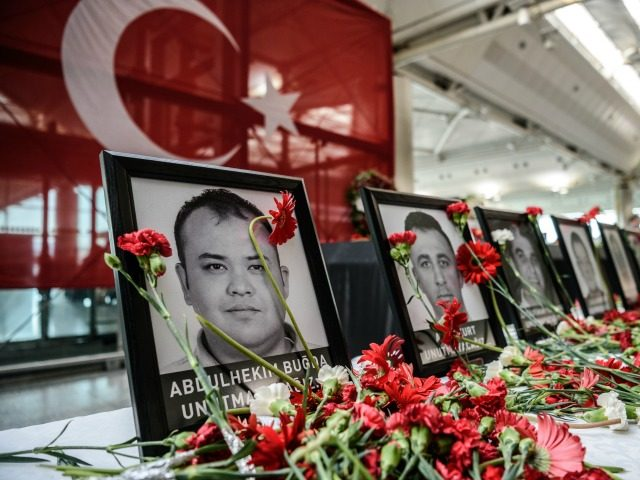 This picture taken on June 30, 2016 shows cloves left by airport employees next to killed airport employees pictures at Ataturk airport international terminal in Istanbul on June 30, 2016 two days after the triple suicide bombing and gun attack occurred at Istanbul's Ataturk airport.
