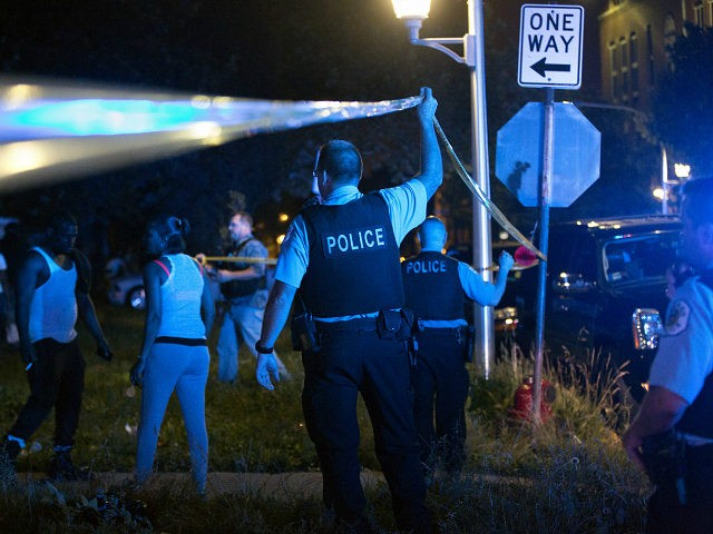 Members of the Chicago Police Department put up tape and clear the scene of a fatal shooting in the 700 block of North Ridgeway Avenue Sunday, June 26, 2016, in the East Garfield Park neighborhood of Chicago. A 55-year-old man who was shot later died at Mount Sinai Hospital and …