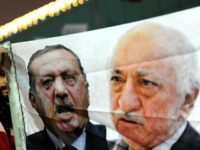 TURKEY, Istanbul : A Turkish protester (L) holds up a banner with pictures of Turkish Prime Minister Recep Tayyip Erdogan (C) and the United States-based Turkish cleric Fethullah Gulen (R) during a demonstration against goverment on December 30, 2013 in Istanbul. Erdogan lashed out at the judiciary as he tried …
